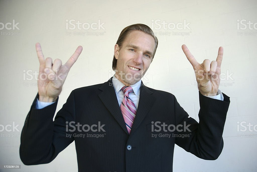 Businessman Rockin with Rock and Roll Sign White Background Businessman trying his best to be cool Achievement Stock Photo
