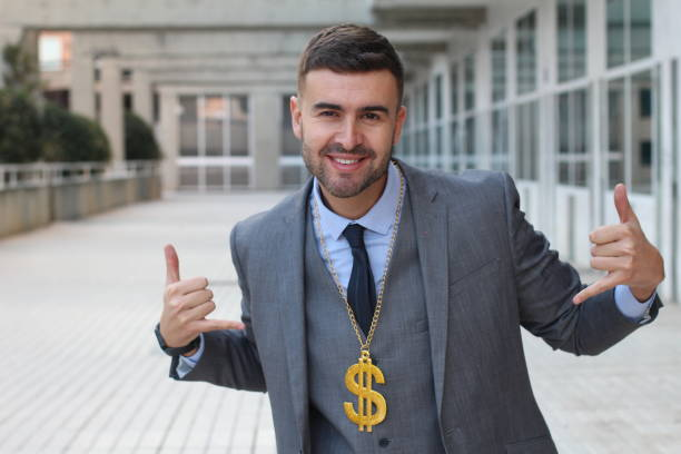 Businessman rocking golden necklace with dollar sign Businessman rocking golden necklace with dollar sign. cheesy grin stock pictures, royalty-free photos & images