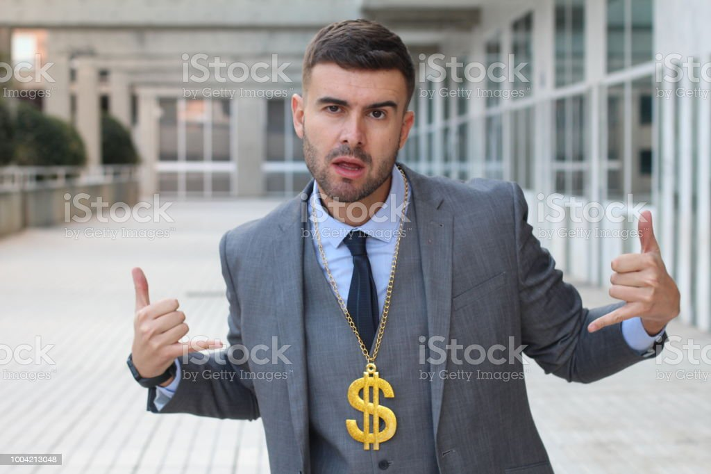 Businessman rocking golden necklace with dollar sign stock photo