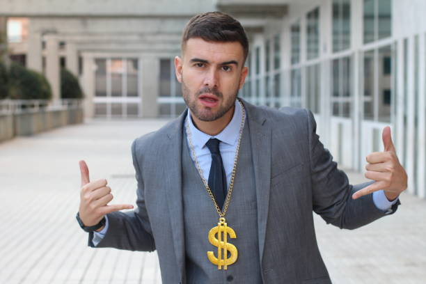 businessman rocking golden necklace with dollar sign - arrogance stock pictures, royalty-free photos & images