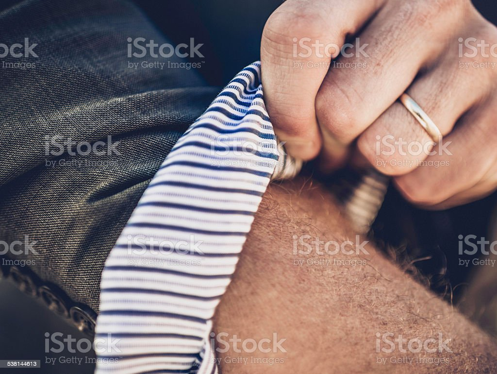 Businessman rolling up sleeves. Getting down to business. stock photo