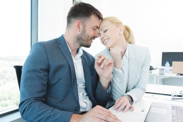 Businessman romancing with pretty secretary at office stock photo