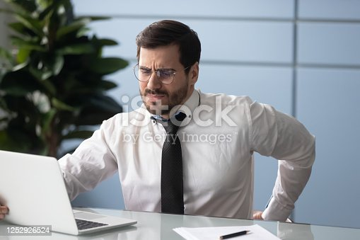 821012164 istock photo Businessman rubbing aching back feels unhealthy, sedentary work concept 1252926524