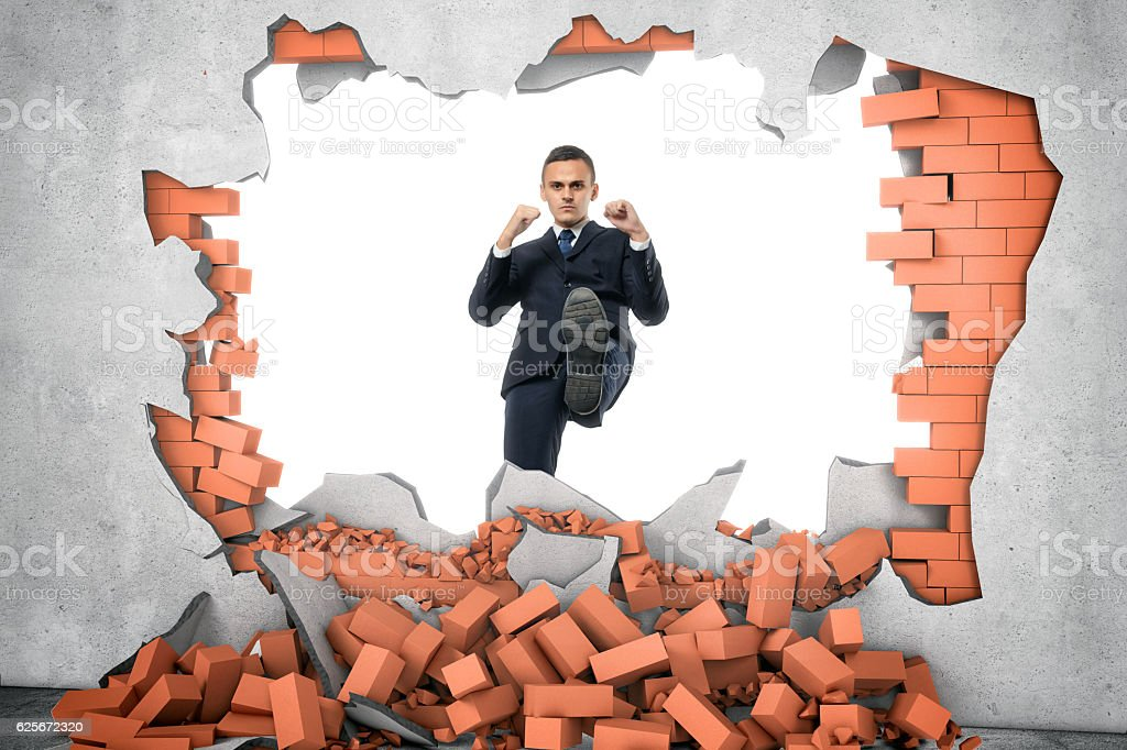 Businessman ruins brick wall with his leg on the white stock photo