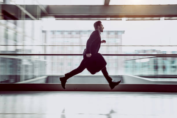 Businessman Running Along The Corridor Businessman Running Across The Corridor beat the clock stock pictures, royalty-free photos & images