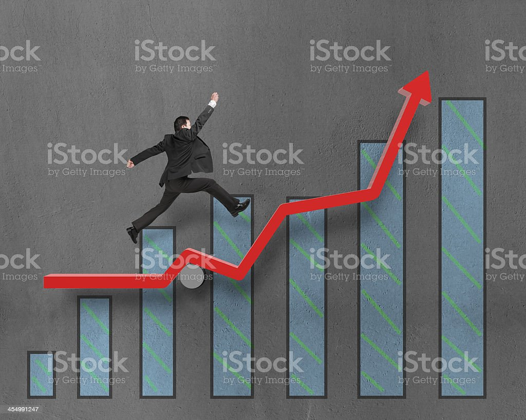 Businessman running and jumping on growth red arrow with chart royalty-free stock photo