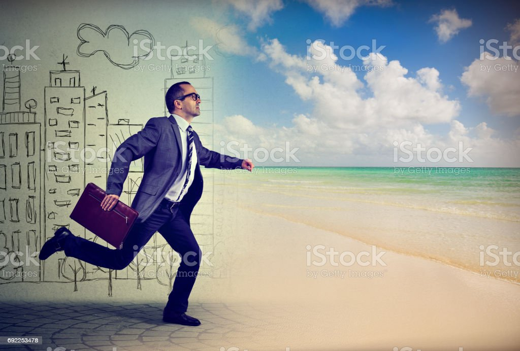 Businessman running away from a busy life in a city to the sunny tropical beach stock photo