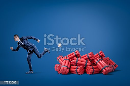 Businessman running away from pack of red tnt dynamite sticks with lighted fuse on blue background. Management and marketing. Financial risks. Business and commerce.
