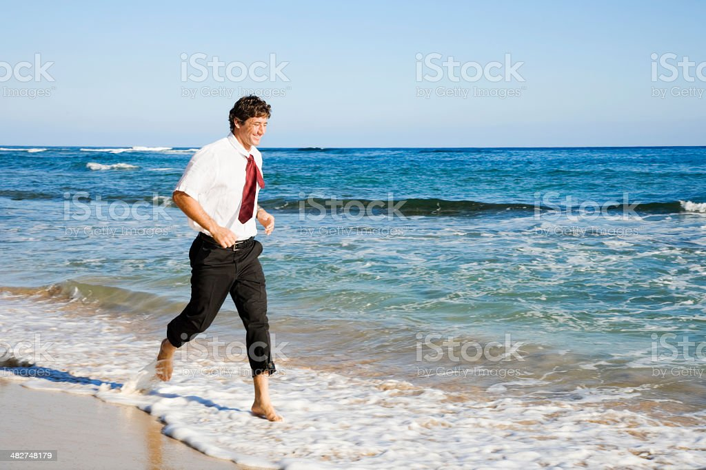 Businessman Running Barefoot on The Beach royalty-free stock photo