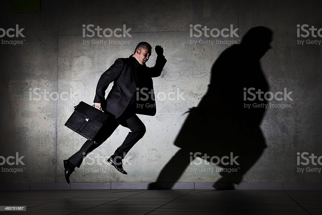 Businessman running by a concrete wall stock photo
