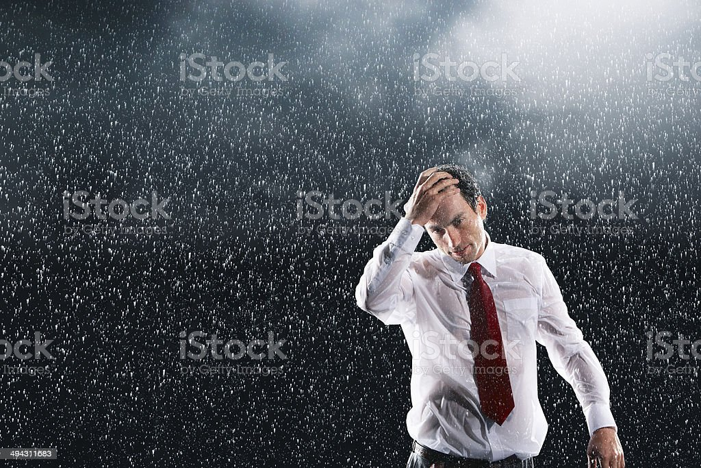 Businessman Running Fingers Through Wet Hair In Rain stock photo