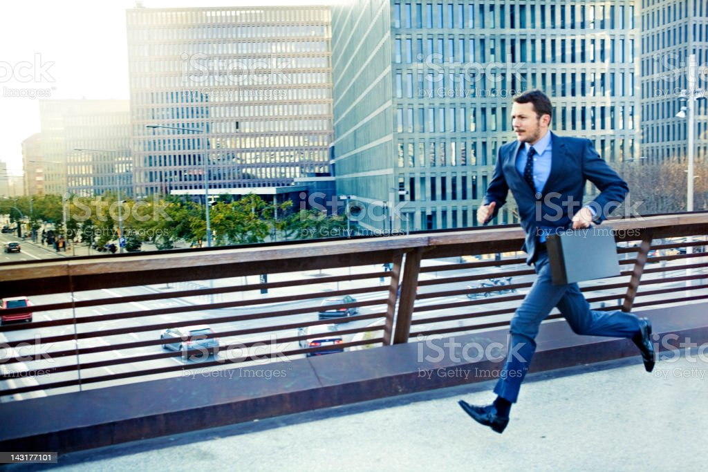 Businessman running in the city stock photo