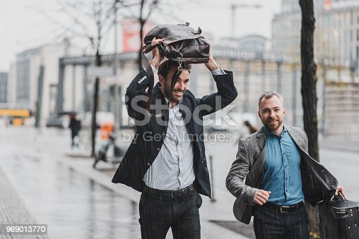 Businessman running in the rain holding a suitcase and a briefcase