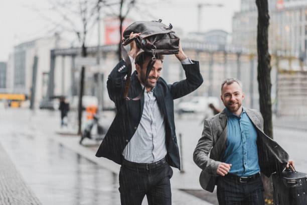 geschäftsmann laufen im regen halten einen koffer und eine aktentasche - deutsche wetter stock-fotos und bilder