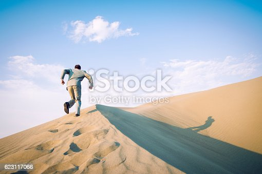 Businessman running up large desert sand dune accompanied by his shadow