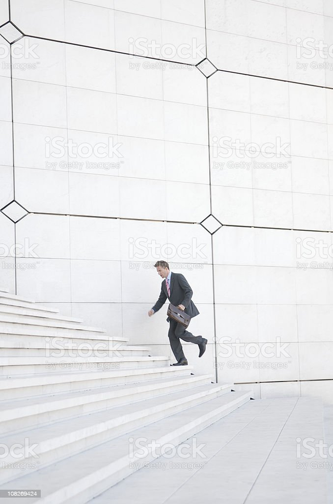 Businessman Running up Staircase stock photo