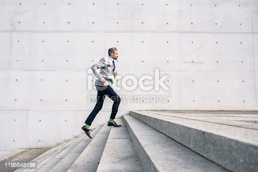 elegant bearded businessman running up stairs  of concrete building