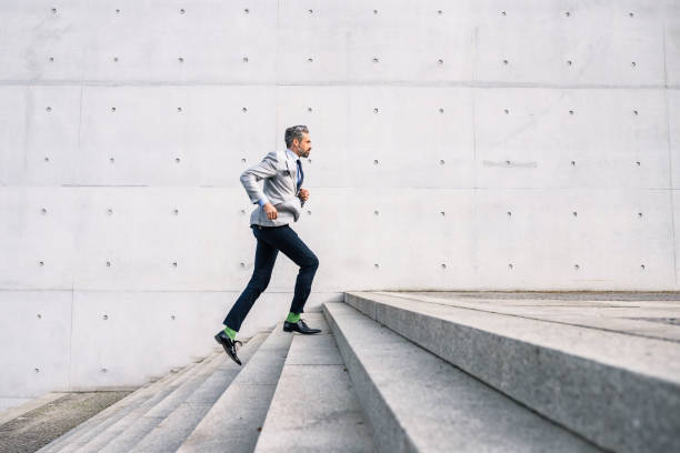 businessman running up stairs outdoors stock photo