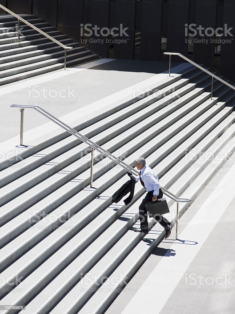 Businessman running up stairs stock photo