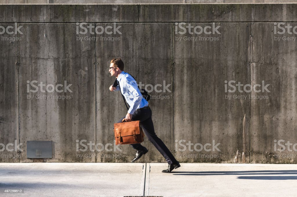 Businessman running with briefcase stock photo