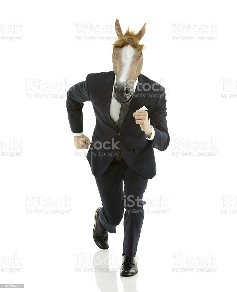 Businessman running with horse's head royalty-free stock photo
