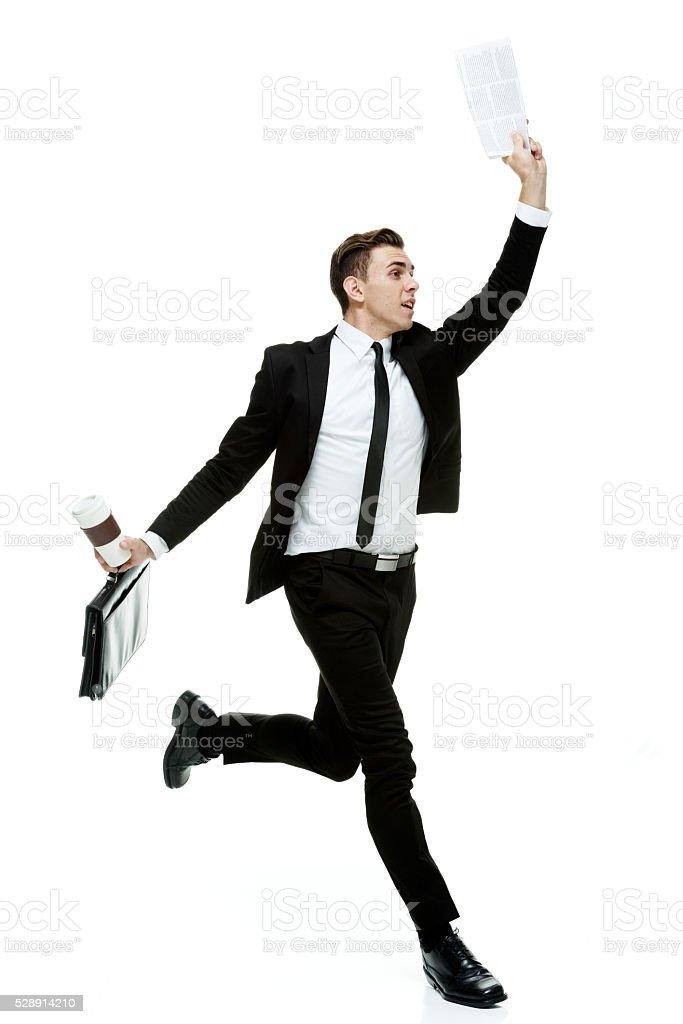 Businessman running with newspaper stock photo