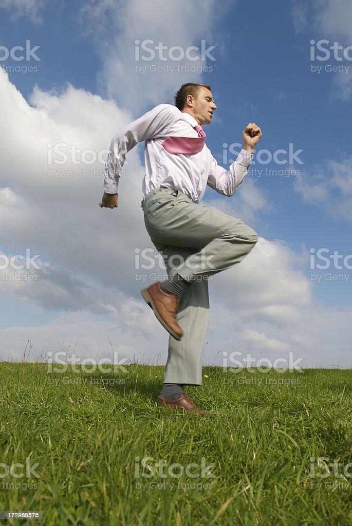 Businessman Runs Across Green Grass stock photo