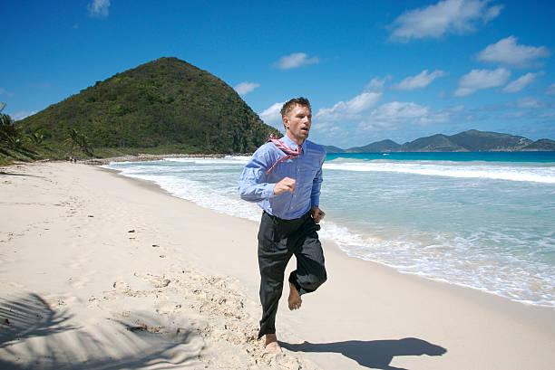 businessman runs along deserted tropical beach - desert island stock photos and pictures