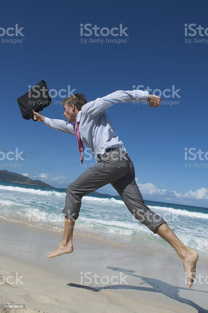 Businessman Runs with Briefcase on Beach stock photo