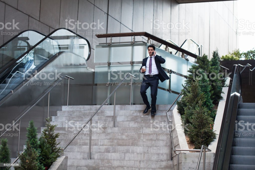 Businessman rushing down stairs talking on phone stock photo