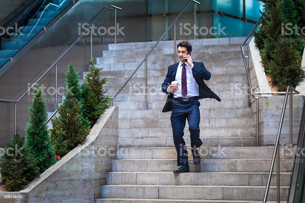 Businessman rushing down the stairs stock photo