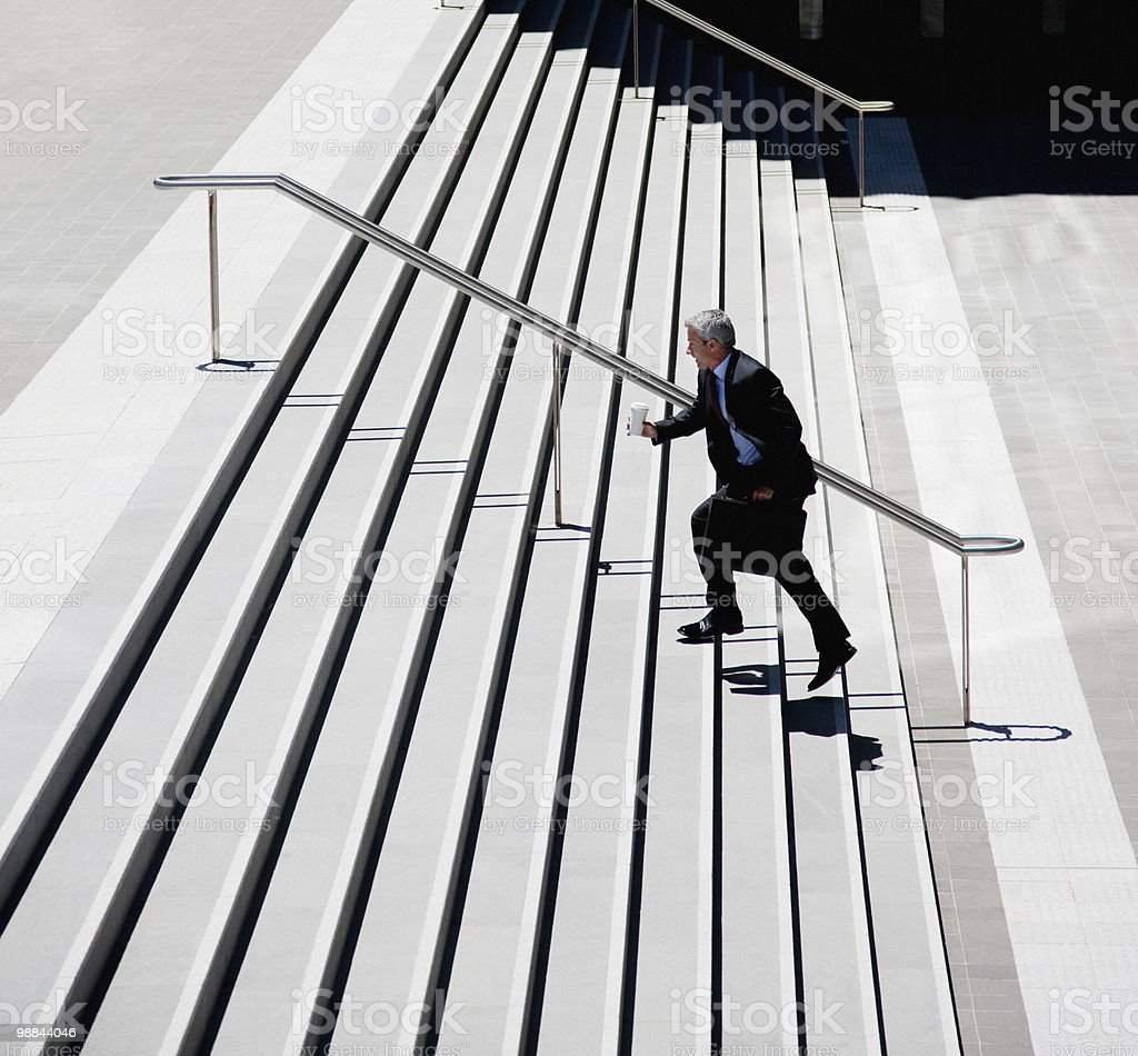 Businessman rushing up steps outdoors royalty-free stock photo