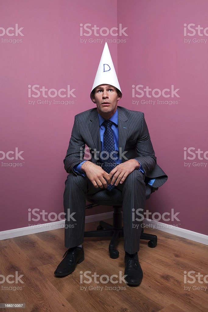 Businessman sat in corner wearing dunce hat stock photo