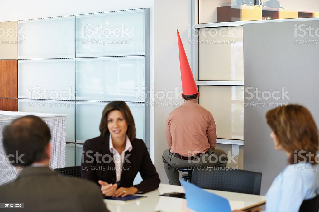 Businessman sat in corner with dunce cap stock photo