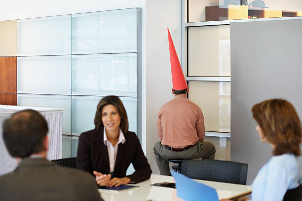 businessman sat in corner with dunce cap - disbarment stock pictures, royalty-free photos & images