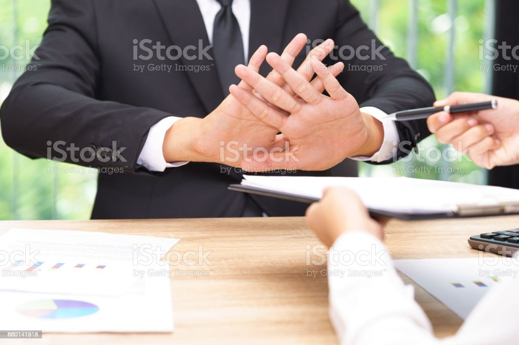 Businessman says no or hold on when businesswoman giving pen for signing a contract stock photo