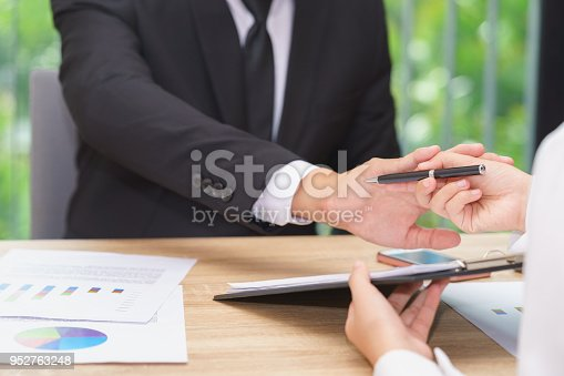 848170878istockphoto Businessman says no or hold on when woman giving pen for signing a contract. 952763248