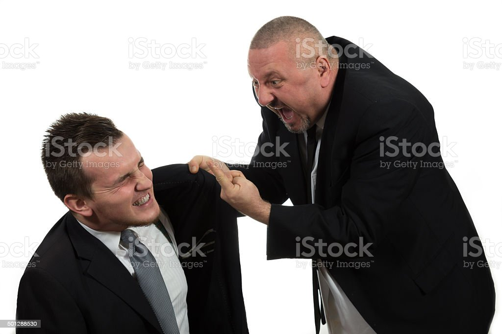 Businessman screaming and fighting at a young colleague stock photo