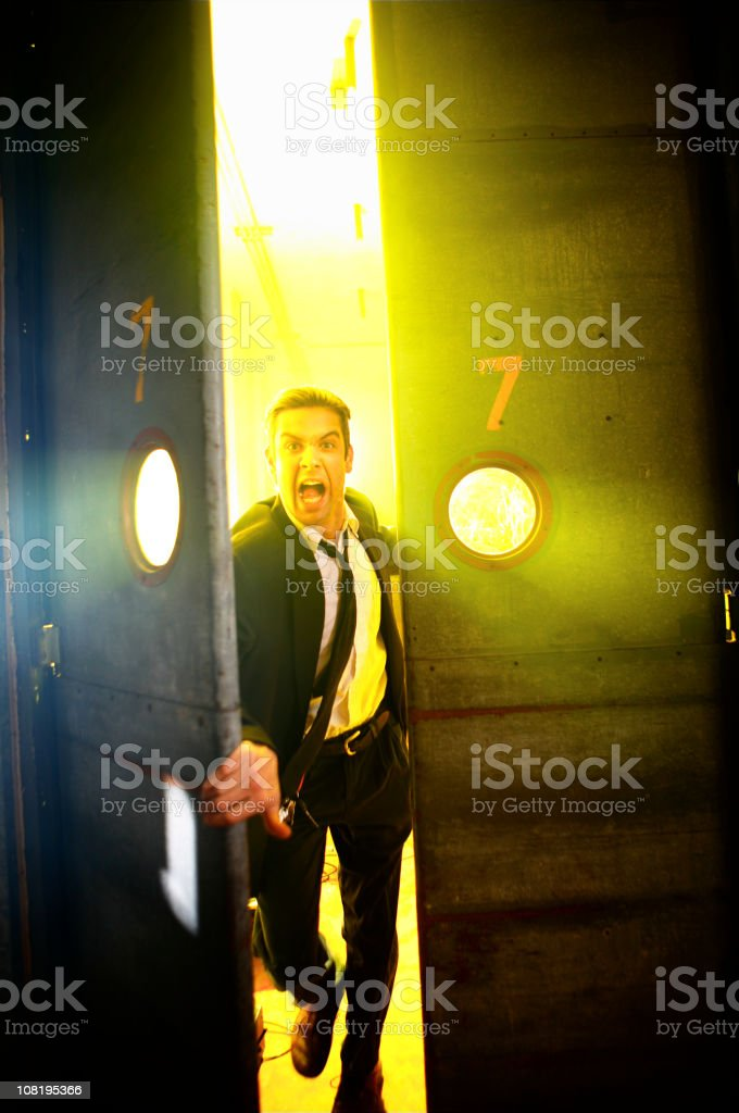 Businessman Screaming and Running Through a Pair of Doors stock photo