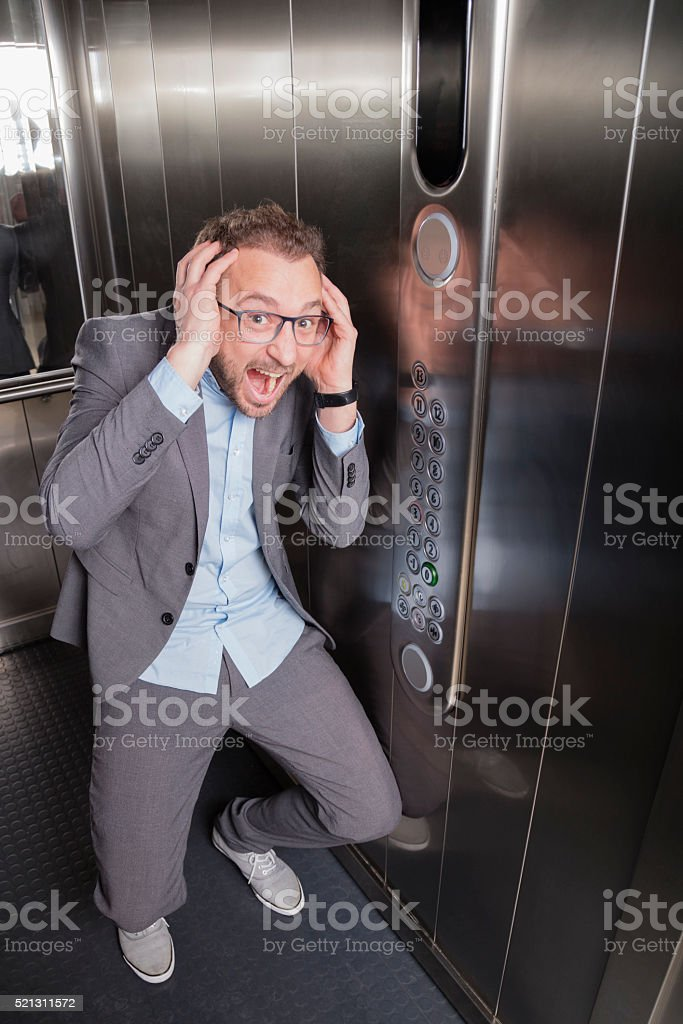 Businessman screaming in the elevator stock photo