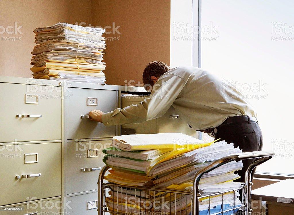 Geschäftsmann Suche nach Dokumenten in Metall-Datei Schränke. – Foto
