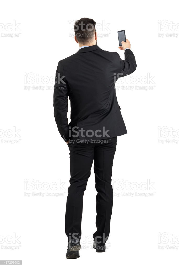 Businessman searching for phone signal rear view or taking photo stock photo