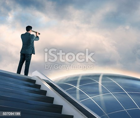 A businessman at the top of a staircase peering through a spyglass at a globe in the distance. Standing atop a futuristic staircase, he scopes out the future contemplating innovation.  A soft halo of light emanates off the wistful globe, with a grid pattern traversing the atmosphere.