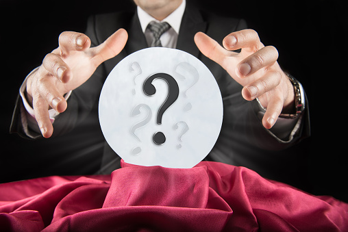 Businessman sees question mark in crystal ball