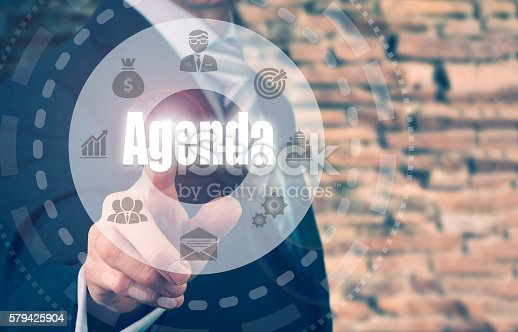 A businessman selecting a Agenda Concept button on a clear screen.