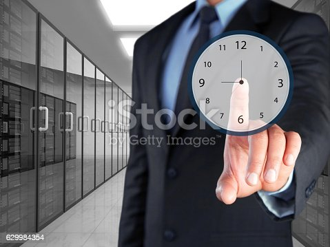 1128981457 istock photo Businessman selecting clock icon on virtual screen 629984354