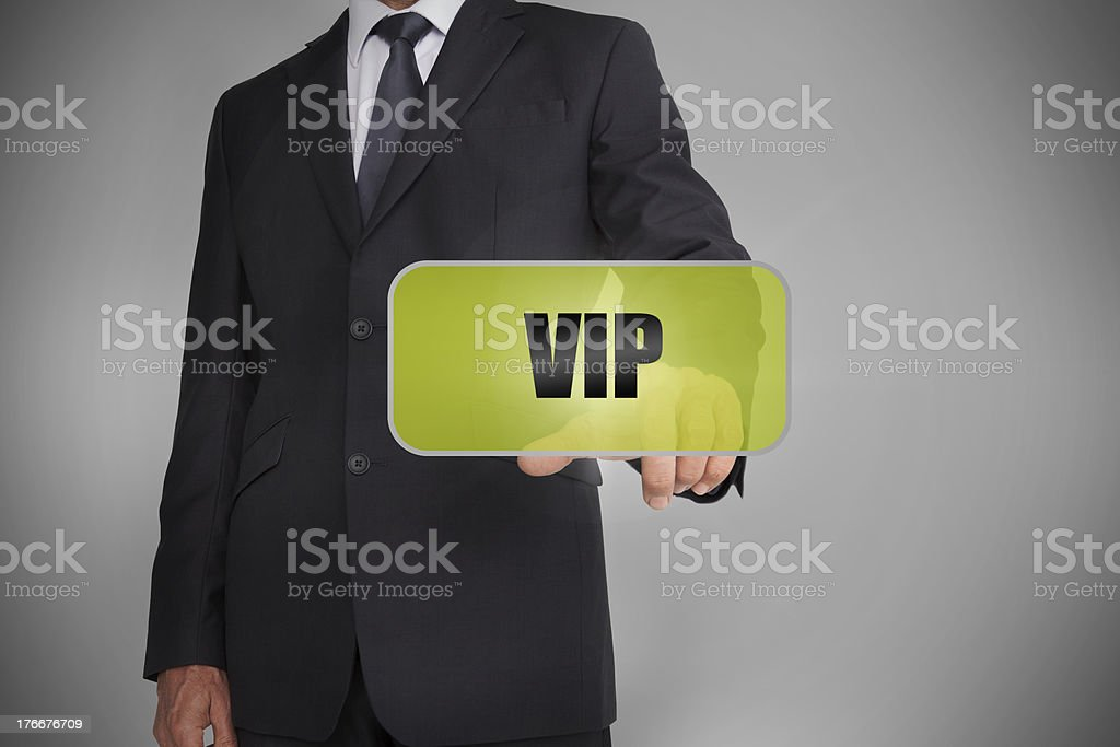 Businessman selecting green tag with the word vip written on royalty-free stock photo