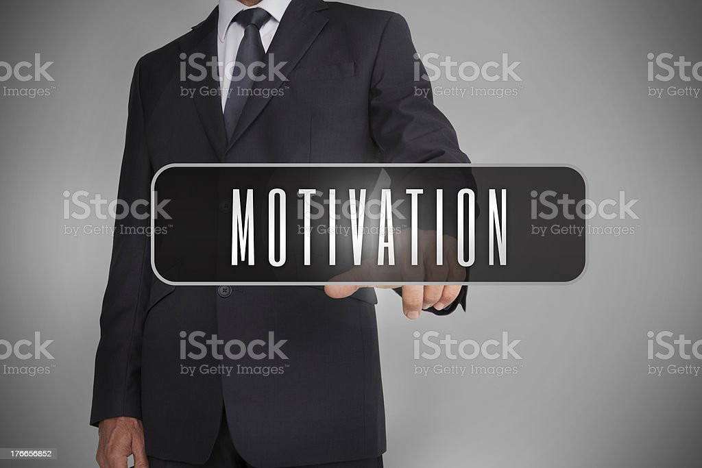 Businessman selecting the word motivation written on black tag royalty-free stock photo
