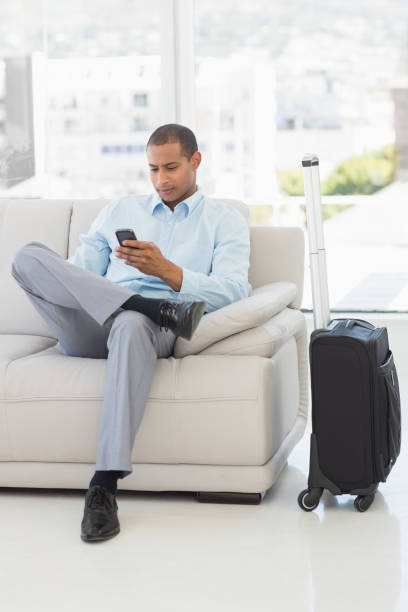 Businessman sending a text sitting on sofa waiting to depart on business trip Businessman sending a text sitting on sofa waiting to depart on business trip in the office depart stock pictures, royalty-free photos & images