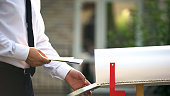 Businessman sending letters and bills, putting them into mailbox near house